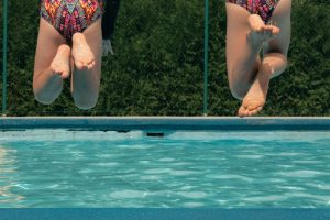 Feet and legs of two friends jumping in pool.