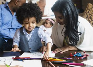 A mother watches a young boy create a colored pencil drawing.